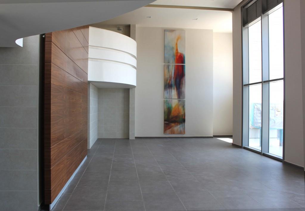 שלושה ציורים אבסטרקט צבעוניים אורכיים בלובי מפואר