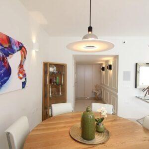 דירה מעוצבת פינת אוכל וציור מעל בכחול על רקע לבן