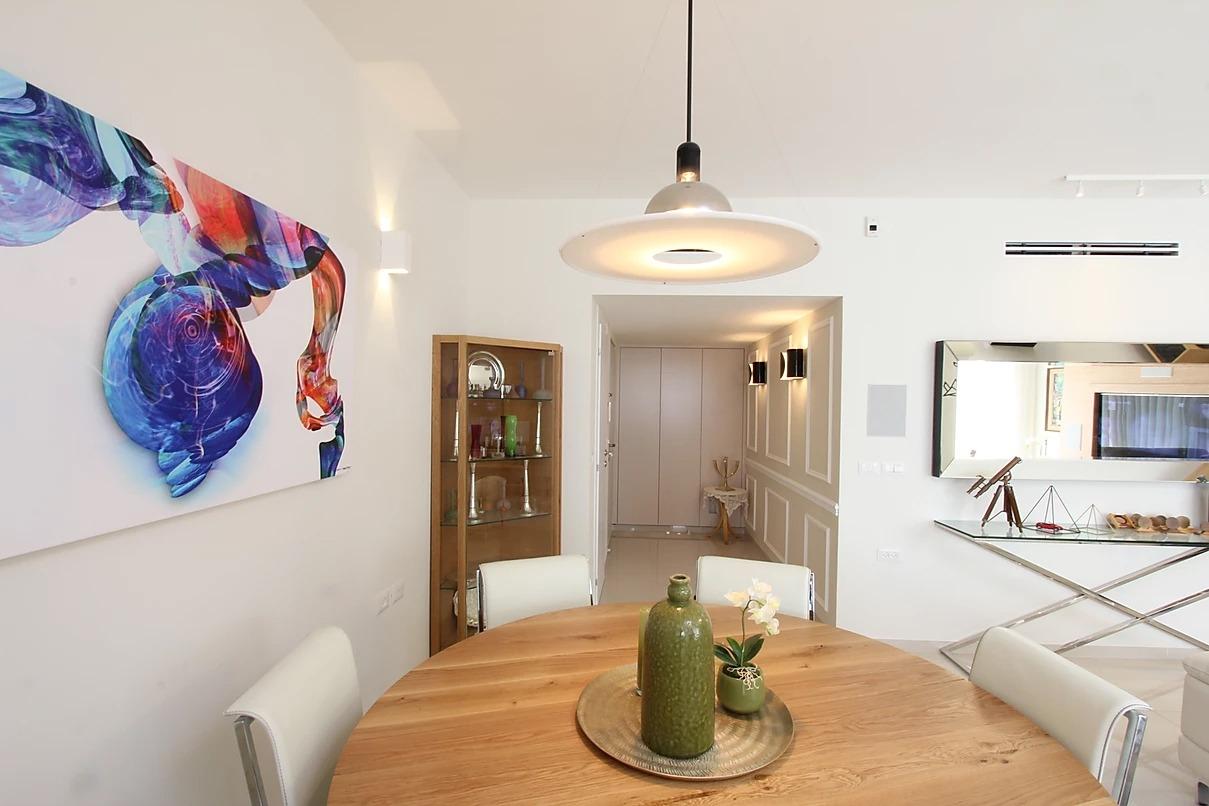 דירה מעוצבת , פינת אוכל וציור מעל בכחול על רקע לבן