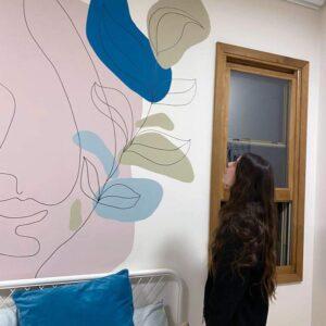 נערה מסתכלת עעל ציור הקיר בהשתאות
