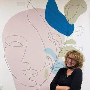 דורית ליד ציור קיר של פני אשה בוורוד, ועלים גרפיים