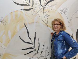 דורית ליד ציור הקיר המיוחד בבית