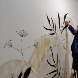 דורית מציירת עלים גרפיים בשחור על גבי קיר