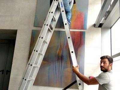 פועלים על סולם מתקינים את הציור בלובי