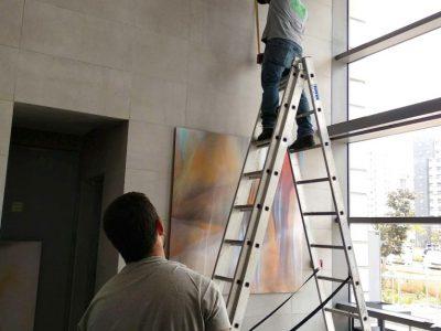 פועלים מתקינים בלובי את הציור השתקפויות