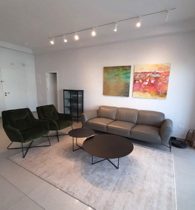 שני ציורים דיגיטליים אבסטרקטים צבעוניים מעל הספה בסלון